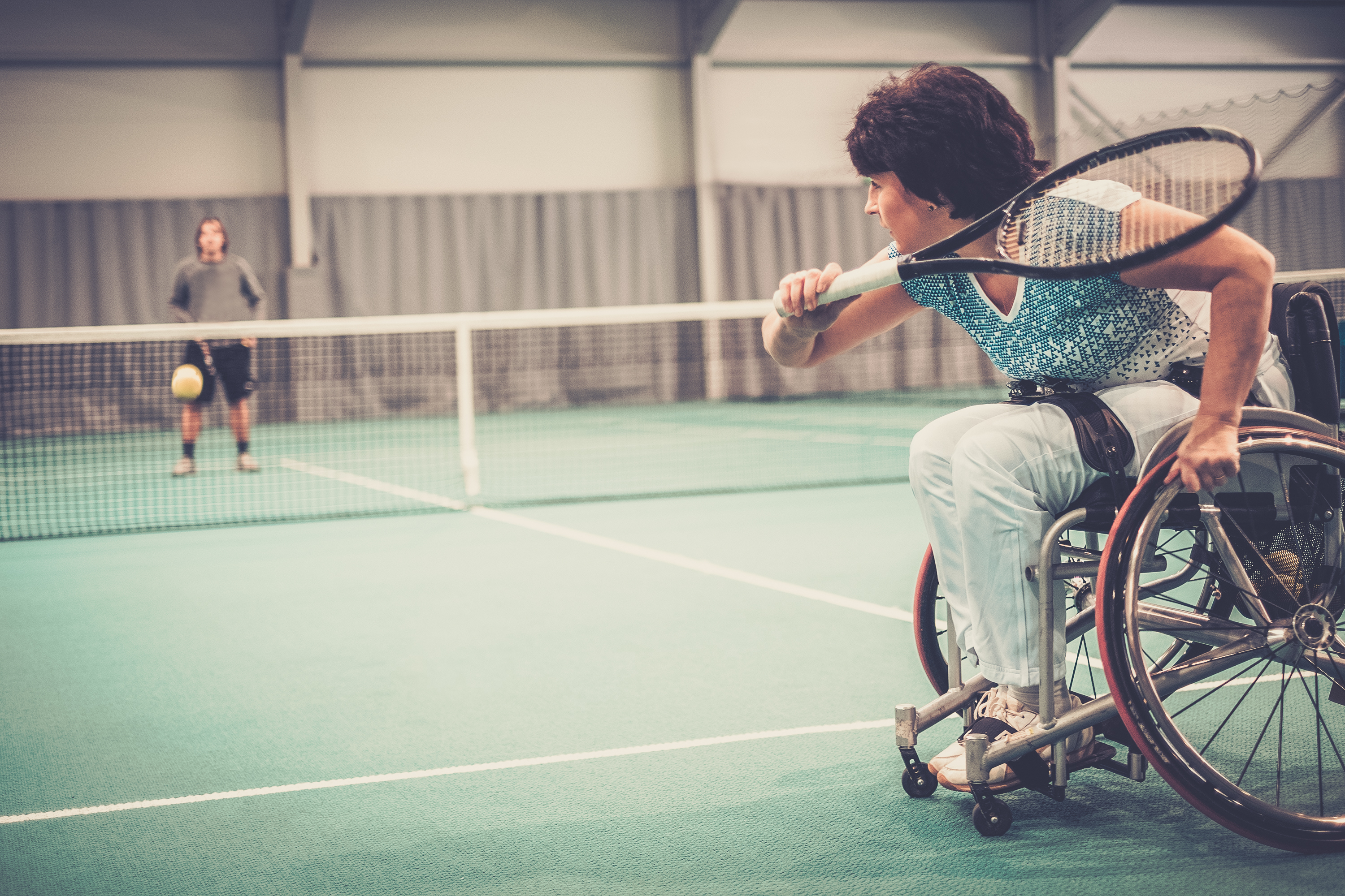 Lady in wheelchair playing tennis