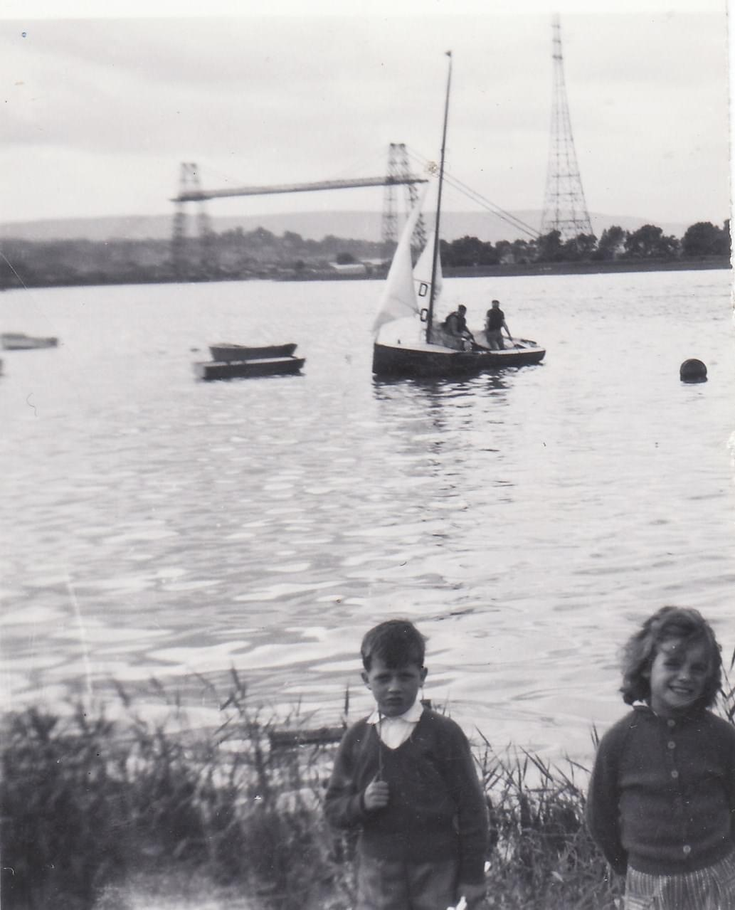 Black and white image of two children in front of water with the transporter bridge in the background
